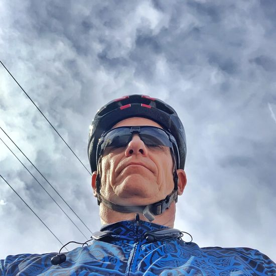 Low angle view of man wearing bicycle helmet against sky
