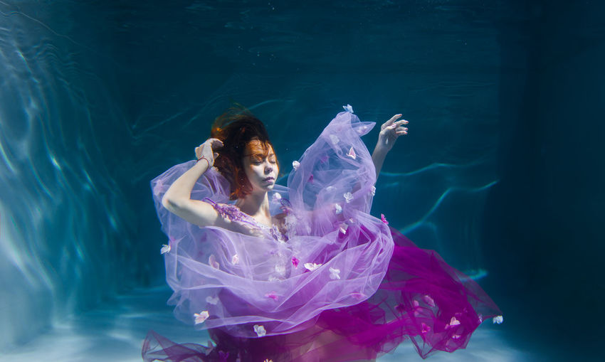 Woman with eyes closed swimming in pool