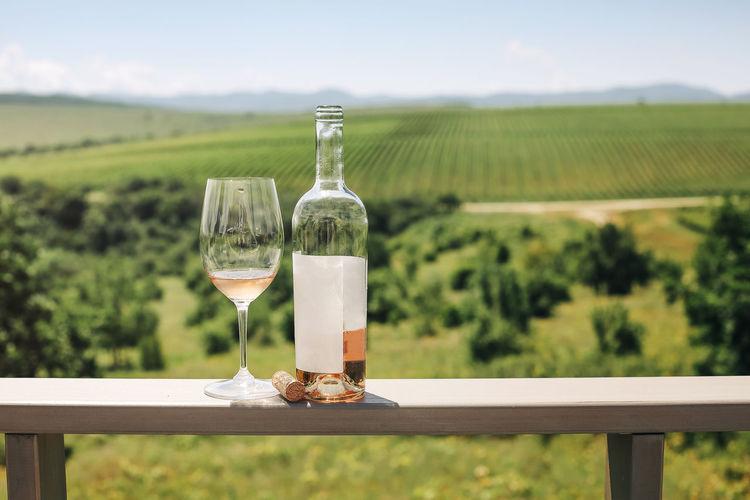Wine glasses on table against sky on field