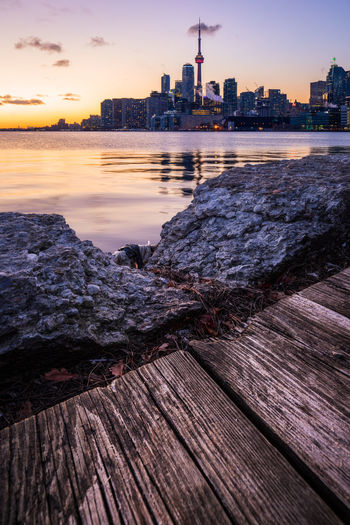 Polson Pier boardwalk and crumbling wall set against Toronto skyline and a calm winter sunset Architecture Built Structure Building Exterior Sky Water Sunset Building City Nature Wood - Material Cloud - Sky No People Urban Skyline Travel Destinations Skyscraper Outdoors Office Building Exterior Landscape Cityscape Toronto Skyline Wide Angle View Foreground