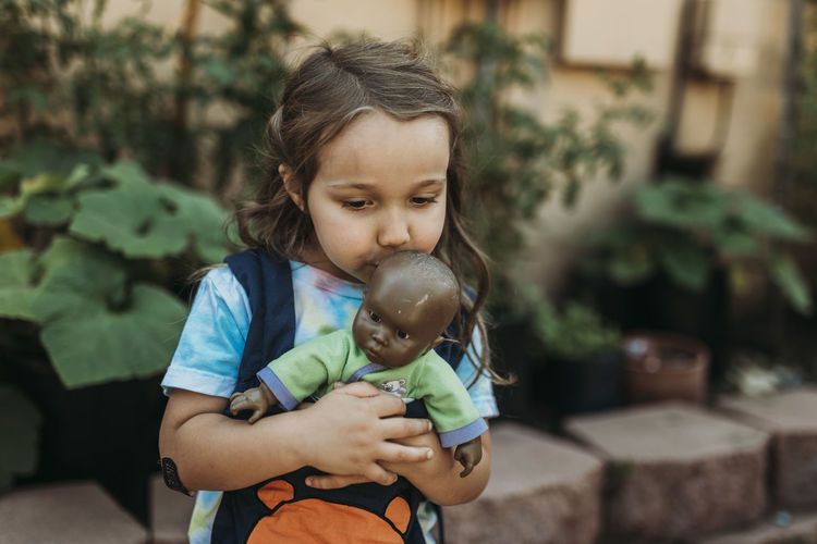 Close-up of cute girl holding baby while standing outdoors