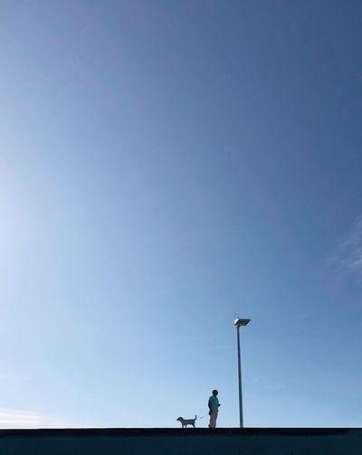 Man on street against clear blue sky