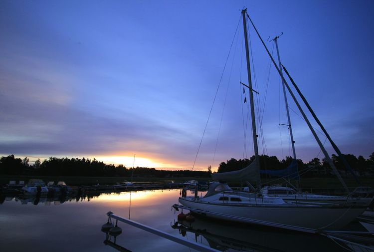 Boats moored at harbor during sunrise