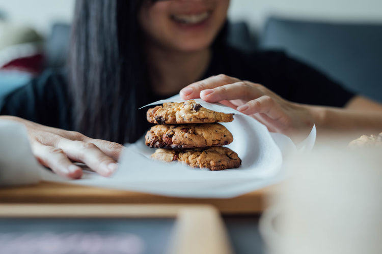 Smiling woman wrapping cookie in paper at home