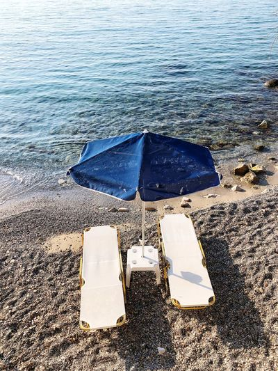 Umbrella Sea Sandy Beach Sunbed Water Sea Nature Beach Land Day Outdoors No People High Angle View Sunlight Sand