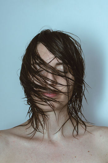 Woman with tousled hair against blue background