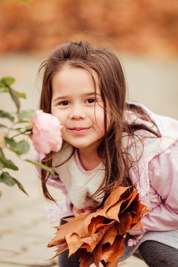 Portrait of smiling girl by rose plant