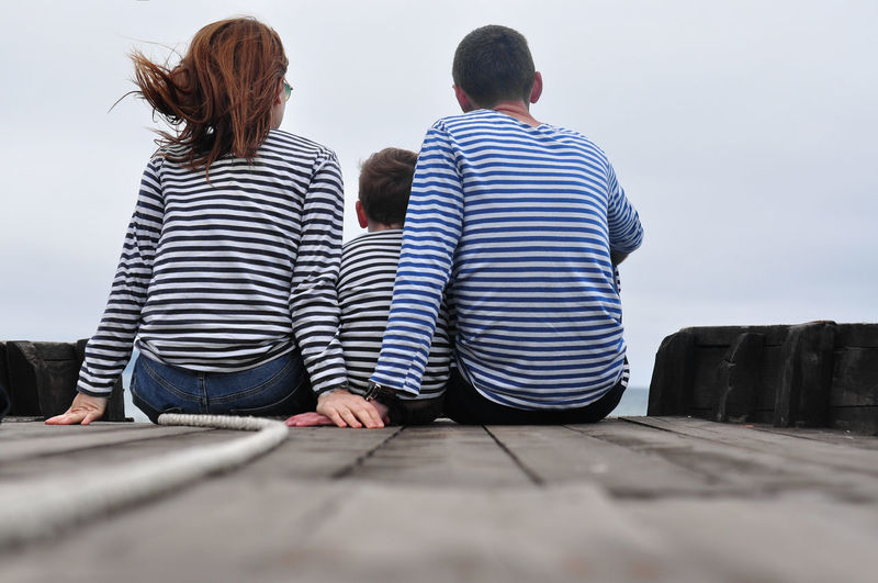 Rear view a family of three, dressed in blue striped longsleeve, holding hands, a child in between