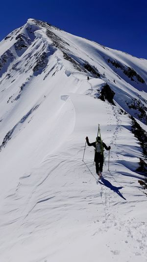 Rear view of man skiing on snowcapped mountain against sky