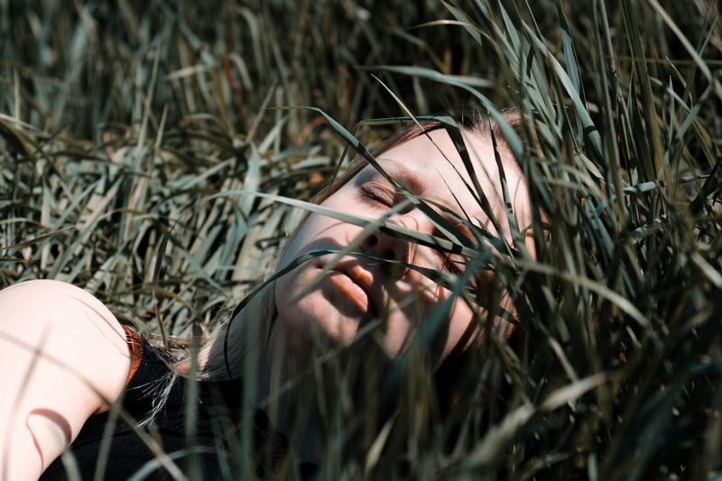 Woman sleeping by grass in sunny day