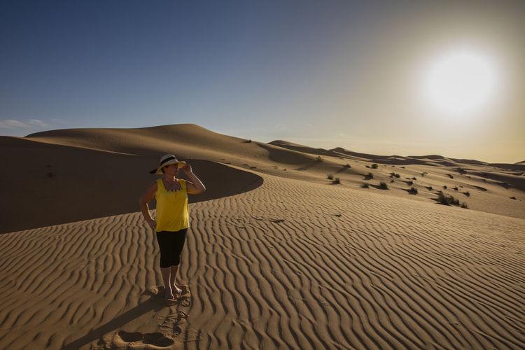 Senior woman standing at desert against clear sky