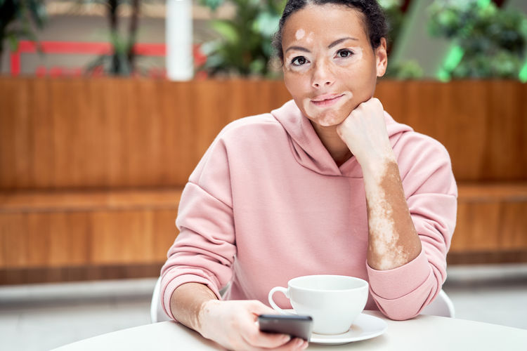 Portrait of woman with coffee cup on table