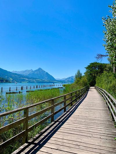 Footbridge over lake against clear blue sky