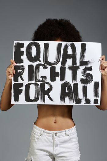 Midsection of woman holding banner while standing against gray background