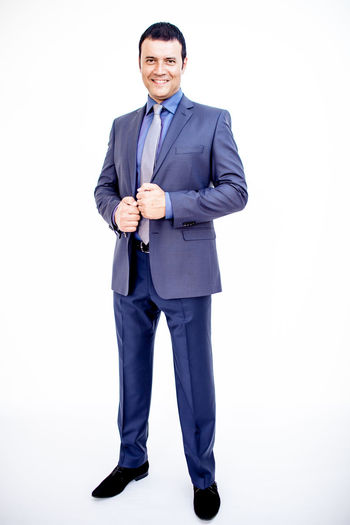Man in classic suit on the white background. Studio shot. Business Business Stories Business Business Finance And Industry Business Person Businessman Clothes Clothing Confidence  Formalwear Front View Full Length Indoors  Looking At Camera Males  Men Menswear One Person Portrait Smiling Standing Studio Shot Suit Well-dressed White Background