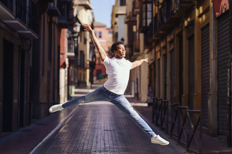 Full length portrait of young man dancing at street