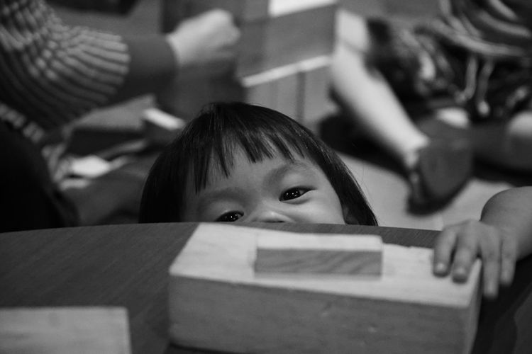 Portrait of cute girl playing with block