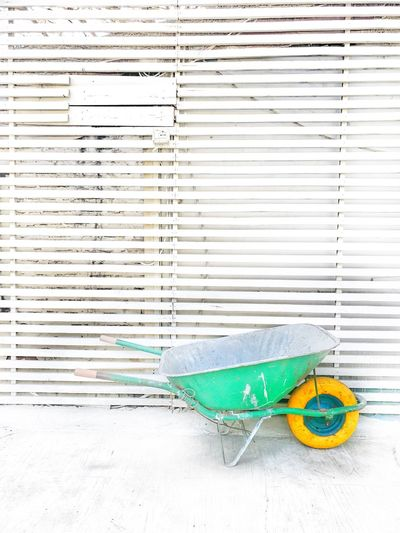 Preparations to summer season in Albania. Bright green wheelbarrow with a yellow wheel with clean white wood background. Albania Outdoors No People Cleaning Equipment Environment Work Working Wheelbarrow Bright Minimalism Minimalistic Albanian Tourism
