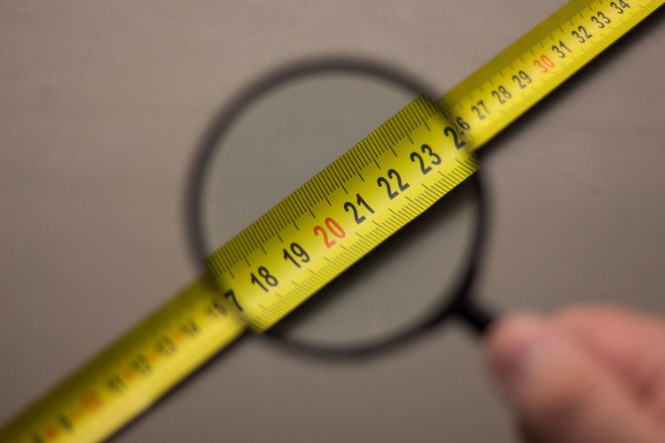 Tape measure seen through magnifying glass held by hand