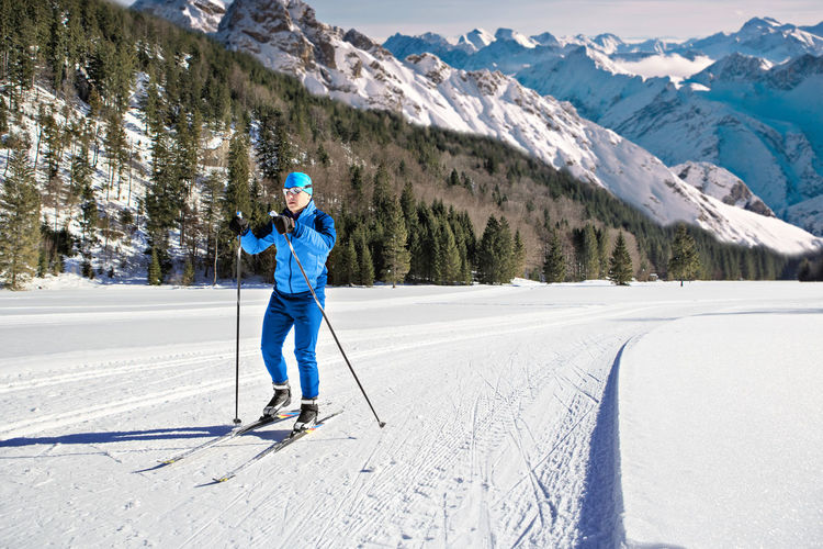Full length of man skiing on snow against snowcapped mountains