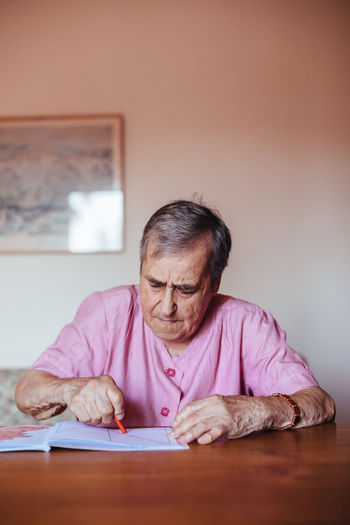 Portrait of mature man sitting on table at home