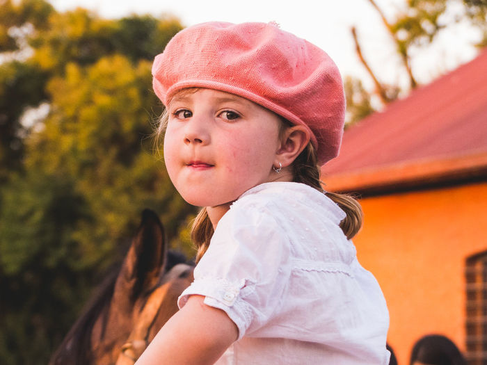 Portrait of girl wearing flat cap against tree