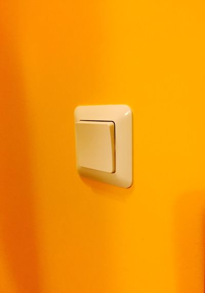 Close-up of light switch on yellow wall