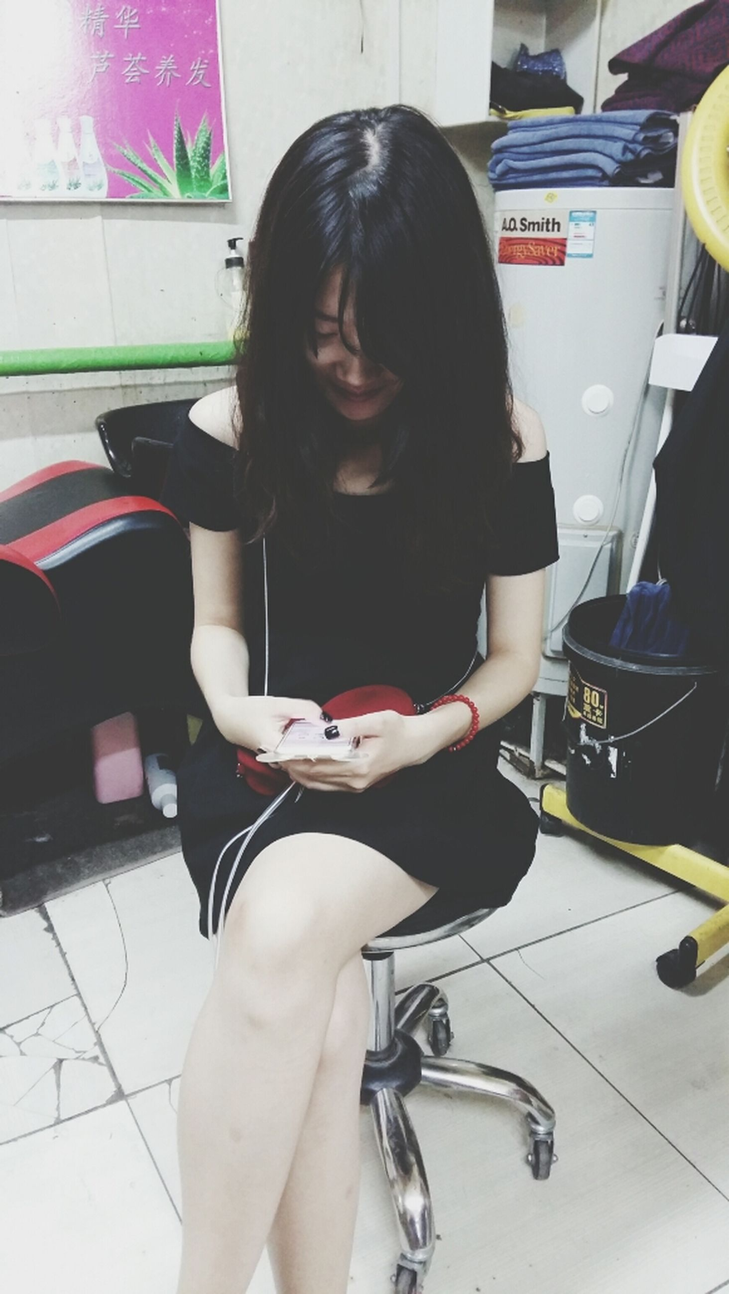 young adult, lifestyles, indoors, holding, casual clothing, person, leisure activity, sitting, young women, front view, three quarter length, wireless technology, standing, technology, looking at camera, communication, side view, long hair