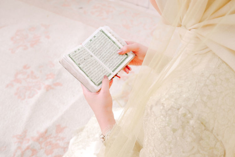Midsection of woman reading koran