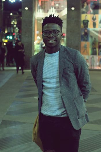 Portrait of young man standing in city