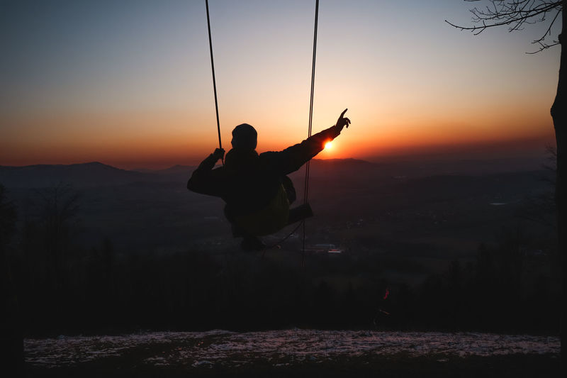 Silhouette man with arms raised against sky during sunset