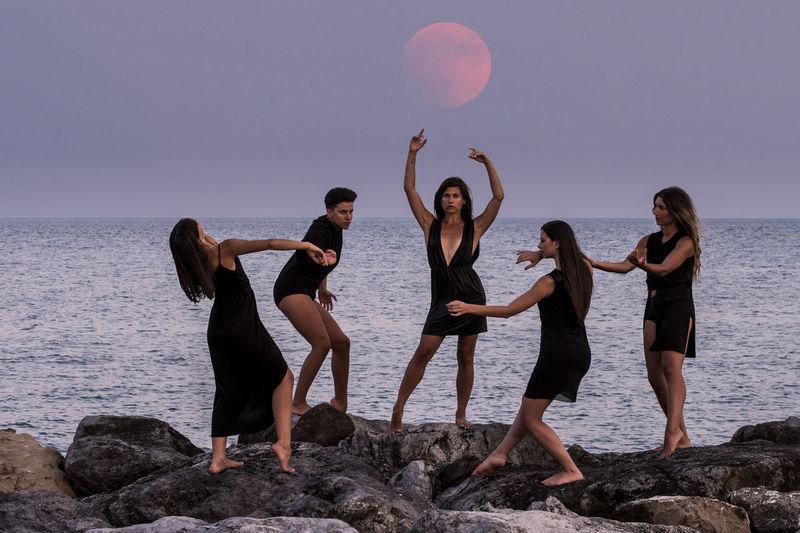 Fashion models posing on rocks by sea against sky