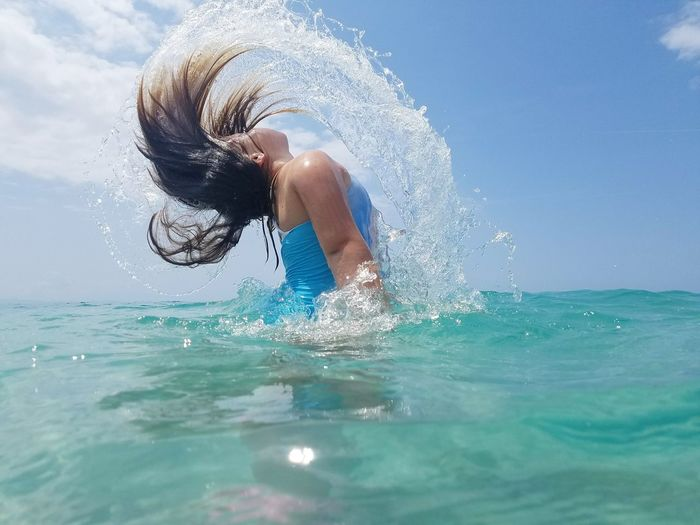 Side view of woman tossing hair in sea