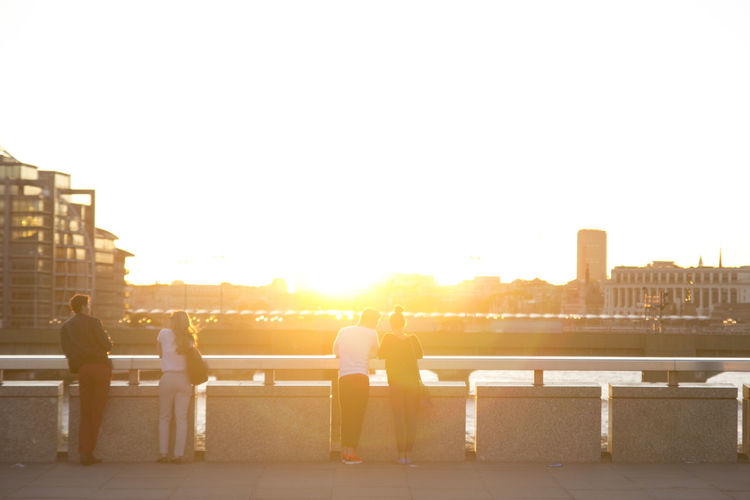 Rear view of young couples standing on bridge during sunset