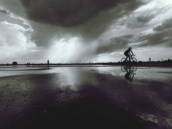 Man riding bicycle on water against sky