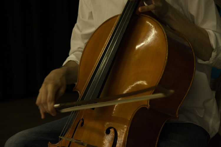 Midsection Of Man Playing Double Bass Against Black Background