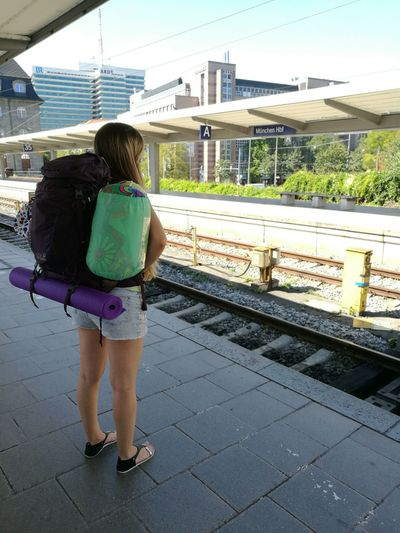 Rear view of woman standing on railroad station platform
