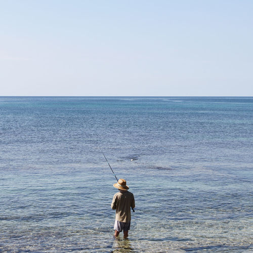 Rear view of man fishing in sea against clear sky