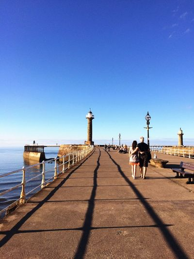 Rear View Of Couple Walking On Promenade By Sea Against Clear Blue Sky