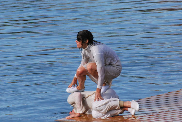 Woman Crouching On Friend Against Lake