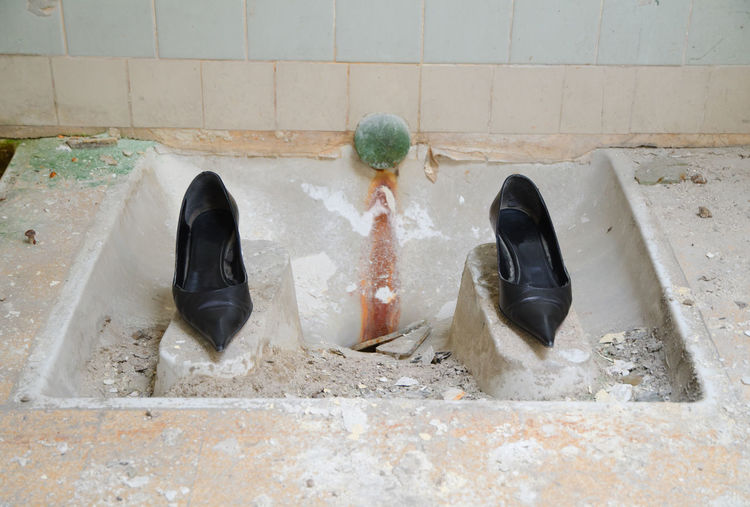 Sandals On Retaining Wall At Bathroom