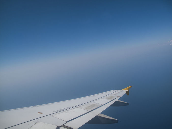 Cropped aircraft wing against blue sky