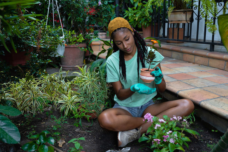 Full length of young woman sitting by potted plant in yard