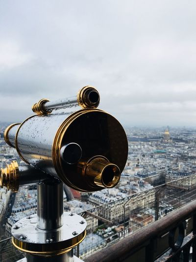 Close-Up Of Coin-Operated Binoculars Overlooking Cityscape Against Sky
