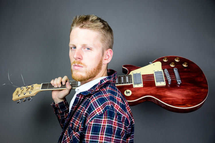 Portrait Of Man Holding Guitar Against Gray Background
