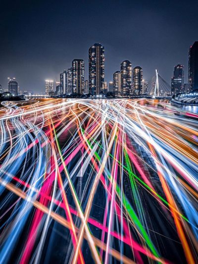 Light trails on street against illuminated buildings in city at night