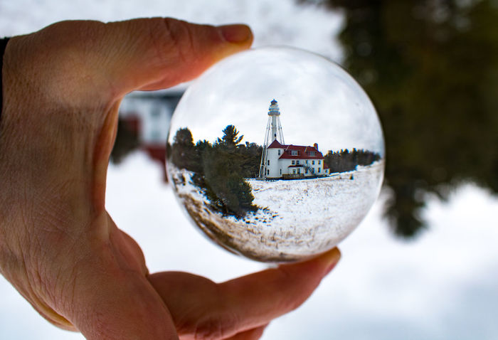 Rawley Point Lighthouse taken using a Lens Ball Lighthouse Rawley Point Light House Wisconsin Architecture Close-up Crystal Ball Day Holding Human Body Part Human Finger Human Hand Lens Ball Magnifying Glass Men Nature One Person Outdoors People Personal Perspective Planet Earth Real People Sky Snow
