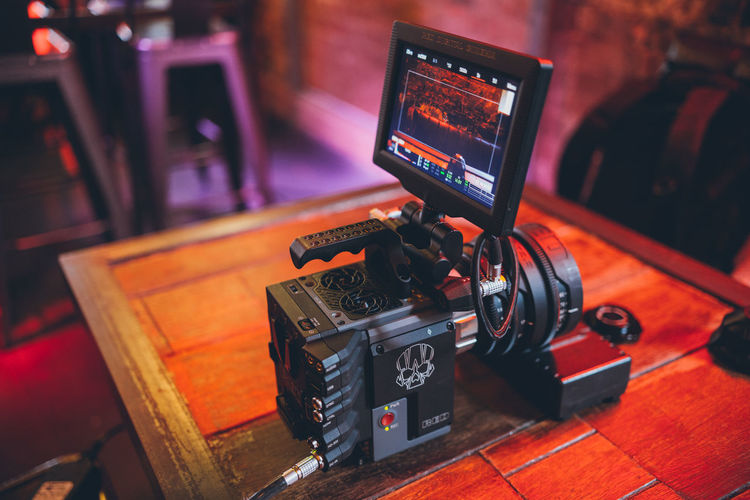Technology Indoors  Photography Themes Focus On Foreground Close-up Camera - Photographic Equipment Communication Arts Culture And Entertainment Table No People Photographic Equipment Wood - Material Camera Still Life Recording Studio Equipment Digital Camera Illuminated Retro Styled Home Video Camera Red Camera Real People Neon Lights Video Camera
