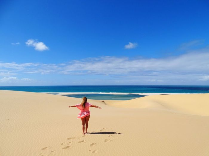 Full length rear view of woman with arms outstretched on beach against blue sky