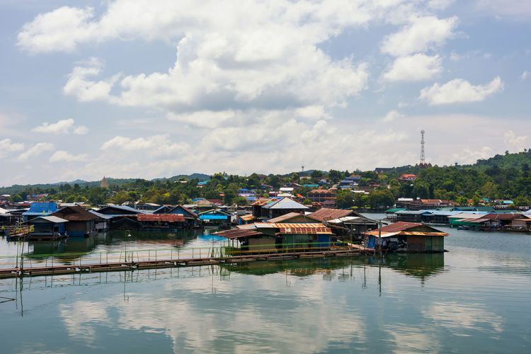 Boats moored in lake by houses against sky